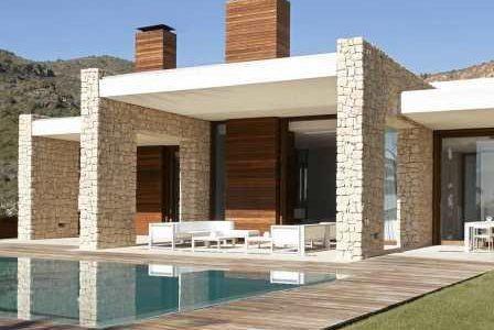 Construção de moradia com fachada revestida a pedra e deck de madeira a envolver piscina.