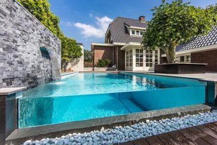 Construção de piscina com parede de vidro.