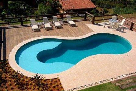 Construção de piscina com formato arredondado e deck de madeira.