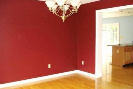 Pintura em sala de estar com paredes vermelha.